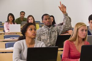 Man in military uniform raising his hand in classroom