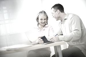 Mature couple doing paperwork using laptop