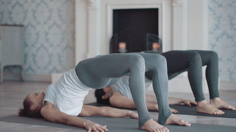 Two women doing yoga's bridge pose.