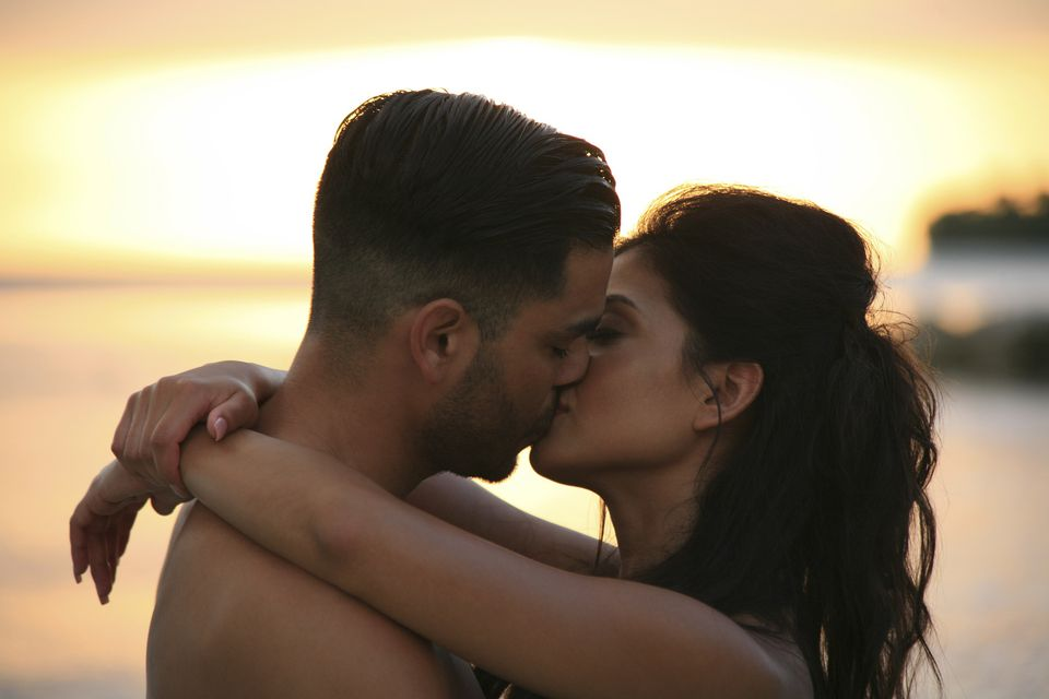 Young Latin couple kissing on beach at sunset