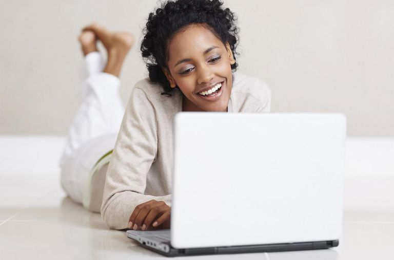 Beautiful happy black woman using a laptop on the floor
