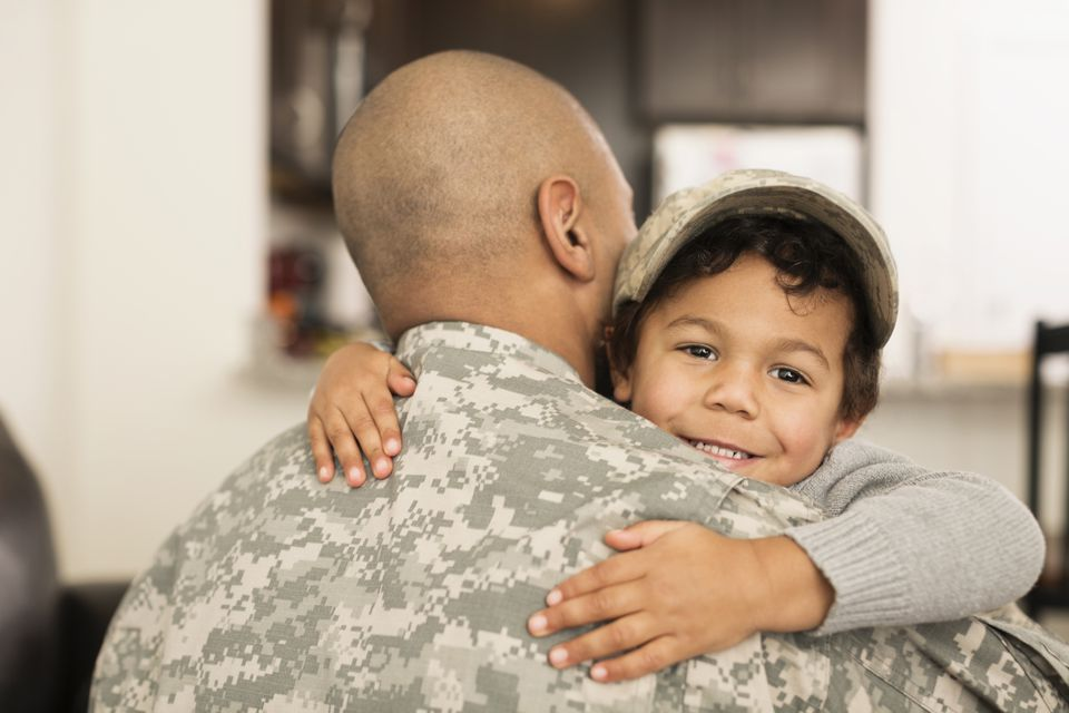 Mixed race soldier hugging son