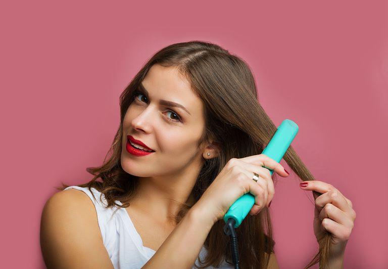 woman using flat iron on hair