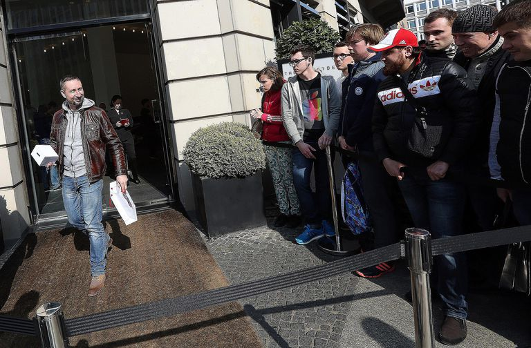 An anxious line of consumers waiting to purchase the first Apple Watch and a smiling man who has purchased one symbolize aspects of consumerist culture.
