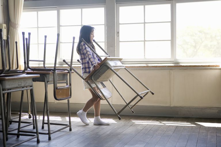 Girl (6-8) carrying desk and chair in classroom