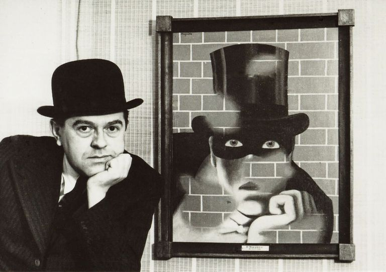 René Magritte posing in front of painting Le Barbare
