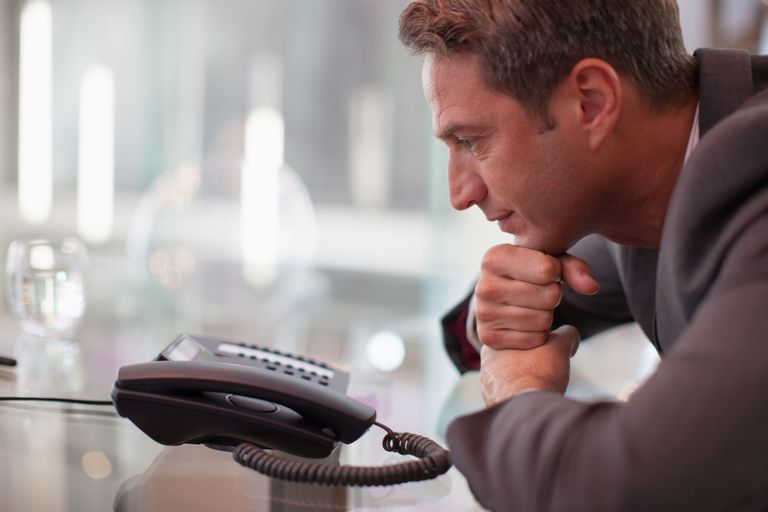 Image of a man waiting for the phone to ring.