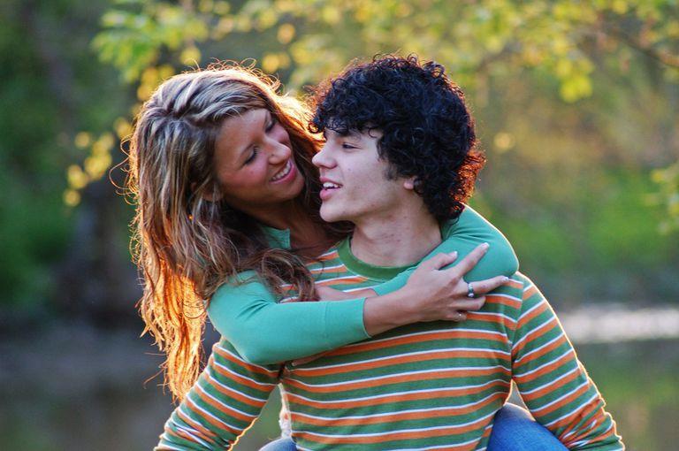 Teen girl hugging boy from behind