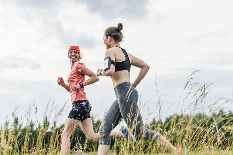 Two women in athletic clothing running in the countryside