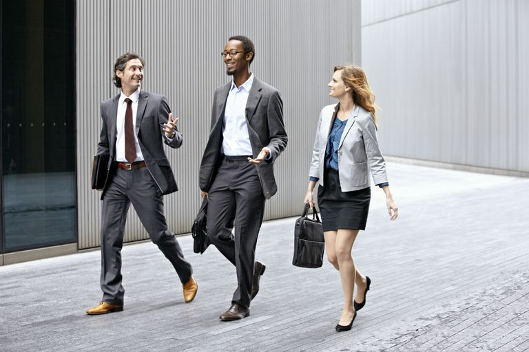 Three business professionals walking quickly