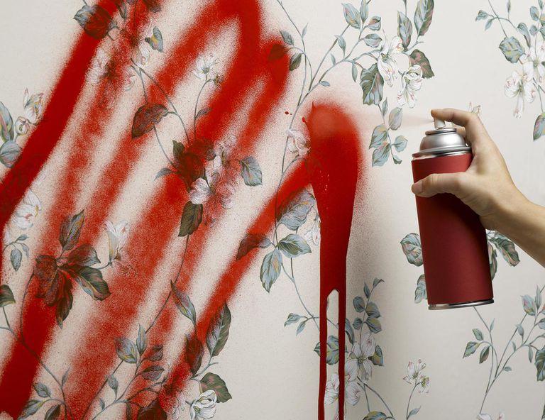 Female hand spray painting wallpaper