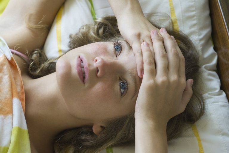 Young woman lying on bed with hands clasped on forehead, looking up in thought