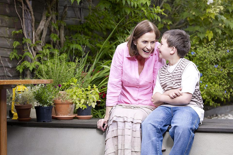 Mum and son sitting on patio in garden