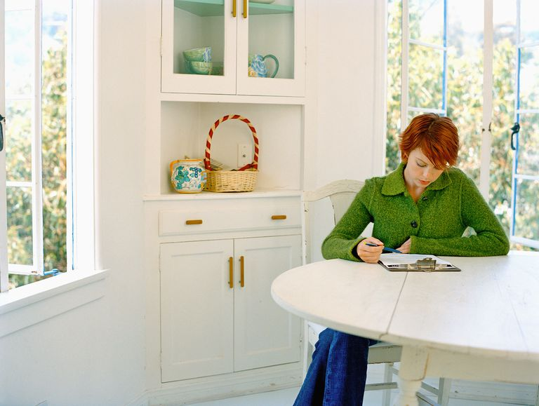 woman looking at checklist on clipboard at kitchen table