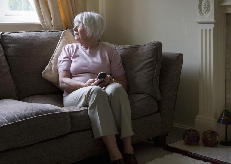 Elderly woman alone on the sofa holding a mobile