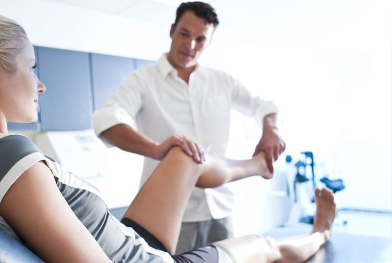 A physical therapist moves a woman's leg