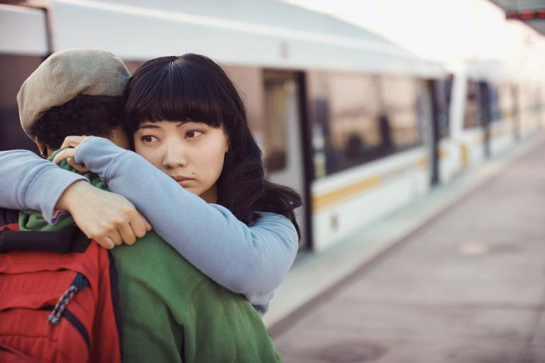 Girl hugging friend at the train station