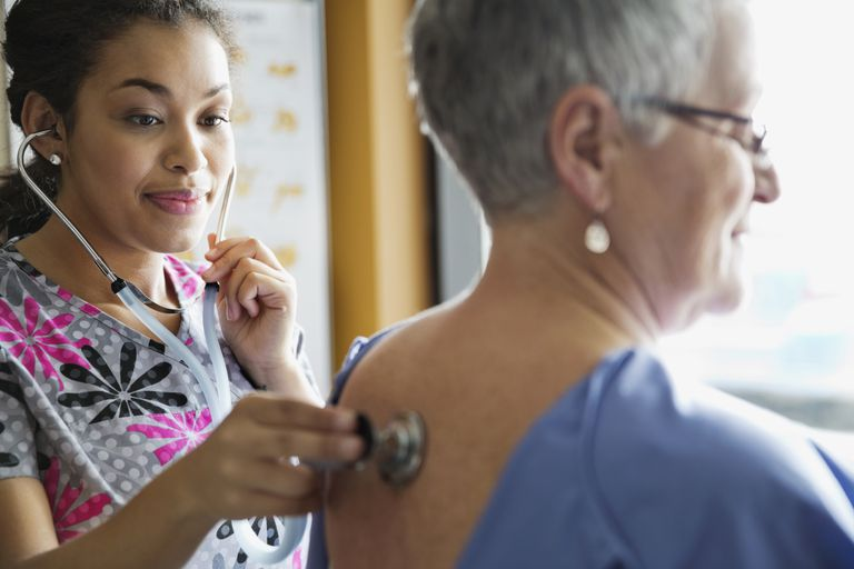 Nurse listening to woman's heart with stethoscope