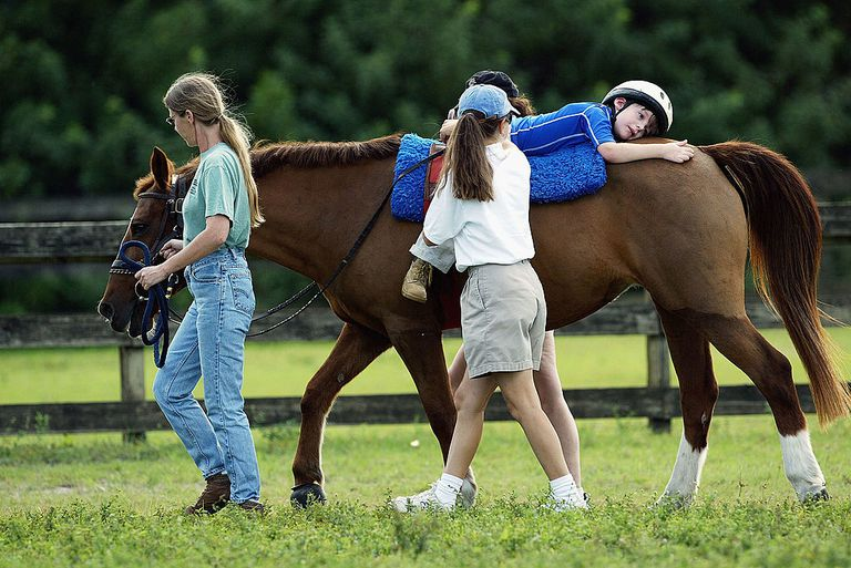 Austistic Boy with Cerebral Palsy Undergoes Horse Therapy COCONUT CREEK, FLORIDA - NOVEMBER 19: Eight year-old Michael Dedrick-Dwyer, who has Cerebral Palsy and Autism, takes 30-minute ride on a horse with therapist Rebecca Reubens and volunteer Kimberly Schuman November 19, 2003 in Coconut Creek, Florida. Michael rides at 'Horses and the Handicap' of South Florida to fight his Cerebral Palsy and Autism. Michael is made to ride on his back and stomach to strengthen his diaphragm which will help him speak better. It also helps strengthen his abdominal muscles. Riding a horse helps Michael to focus longer and recognize his surroundings. 'Horses and the Handicap' have served the handicapped with horse therapy for 23 yrs. The stable has 10 horses, 70 students and over 200 volunteers. The ages of the students range from four years-old to 66 years-old. Until he was four years-old, Michael had to use a wheelchair to sit-up. Then his mother discovered 'Horses and the Handicap' and now Michael can ride a horse, hands free.