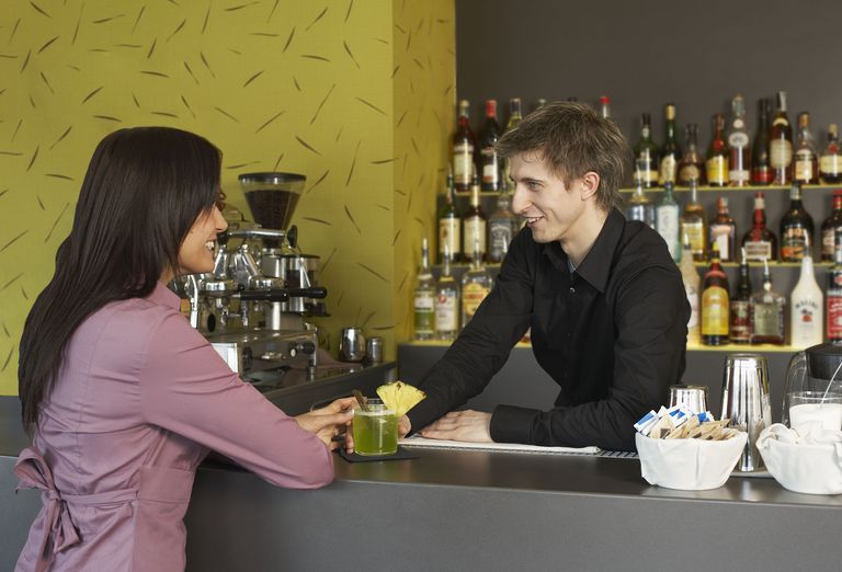 Young woman talking to bartender in Italy
