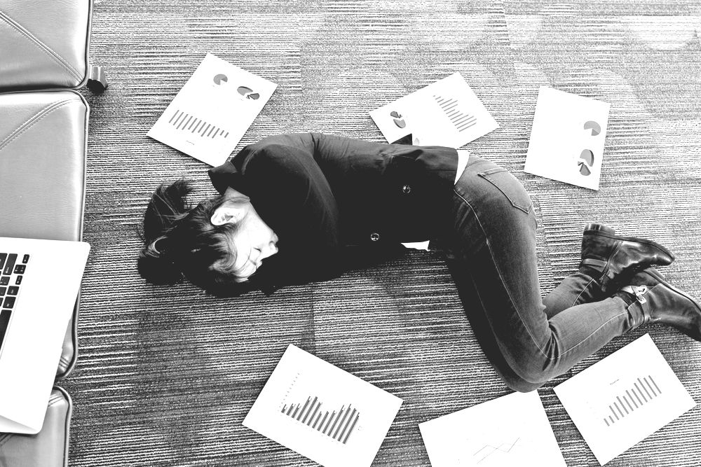 entrepreneur asleep on the ground surrounded by papers