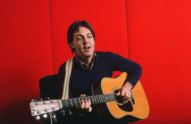 Paul McCartney as he plays acoustic guitar against a red background, October 7, 1984.