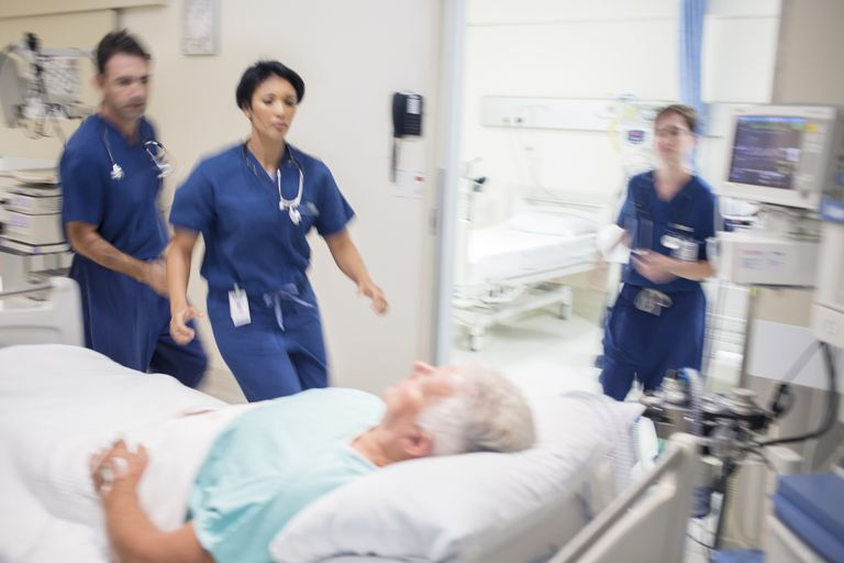 Man in hospital bed with doctors around
