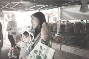 Mom grocery shopping with baby at market