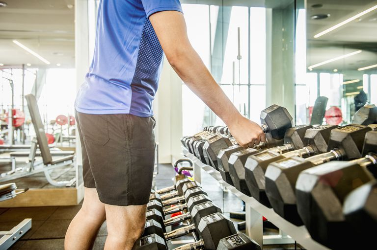 man picking up dumbbell from weight rack in gym