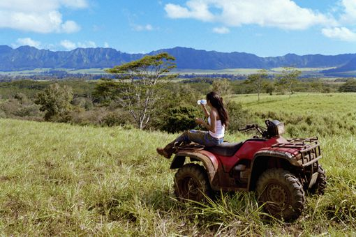 Young woman drinking water on the back of an ATV