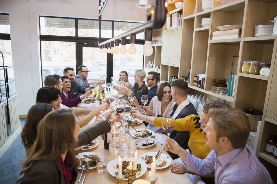 Friends toasting wine glasses at restaurant table