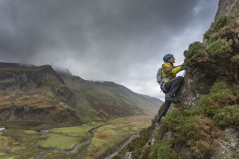 Female mountaineer climbs steep mountainside