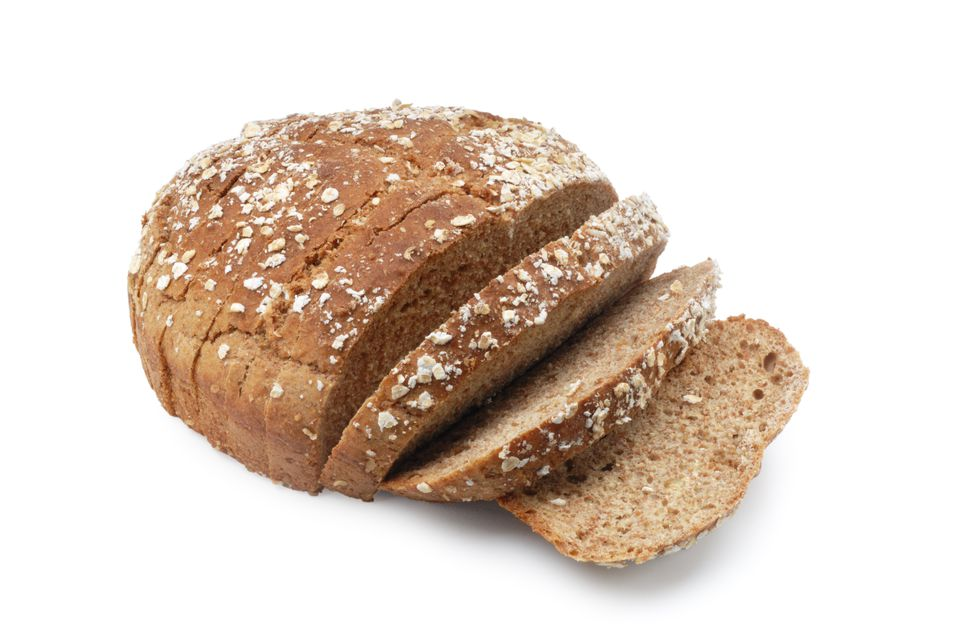 A loaf of brown sesame seed bread with three slices cut