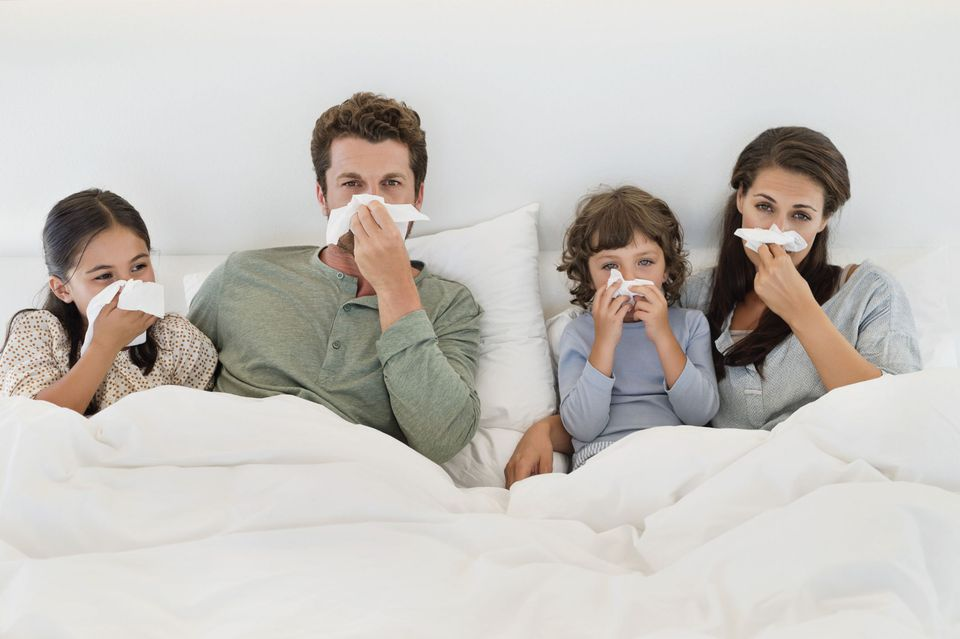 A picture of a mom, dad and kids who are sick