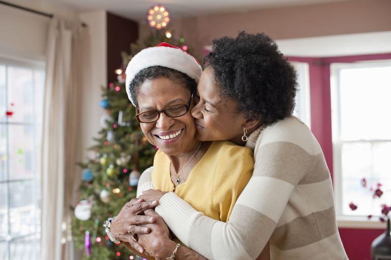 Mom and daughter embracing near Christmas tree