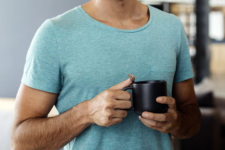 Portrait of smiling man drinking coffee at home