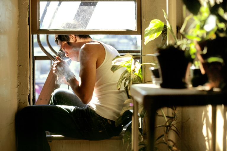 A young man sits in a window lighting a cigarette