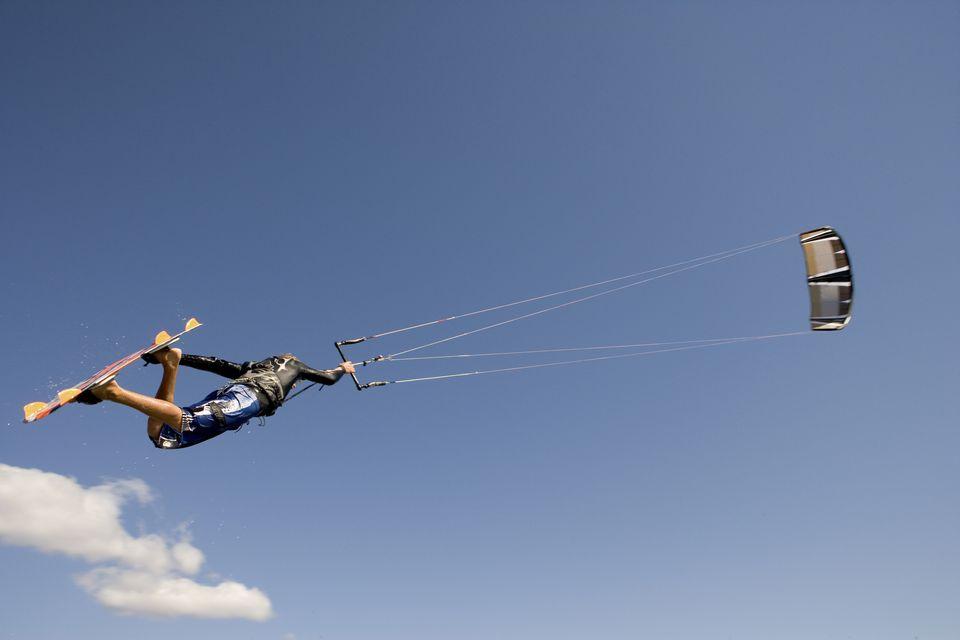 Kite boarder sailing through air.
