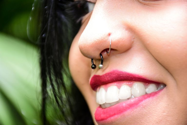 Close up of woman's nose and septum piercings
