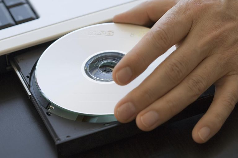 Mature putting CD in laptop drive, close-up of hand.