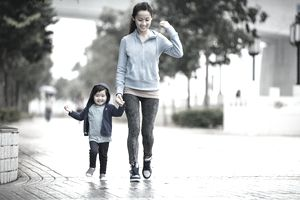 Mom and toddler child joyfully walking through the drizzle.