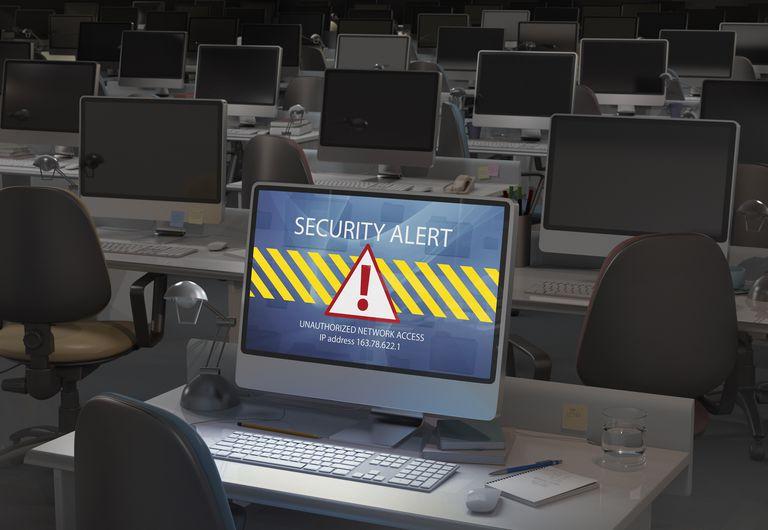 Computer in dark office, security alert on screen