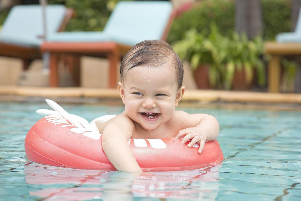 Thailand, happy baby girl with floating tire in swimming pool