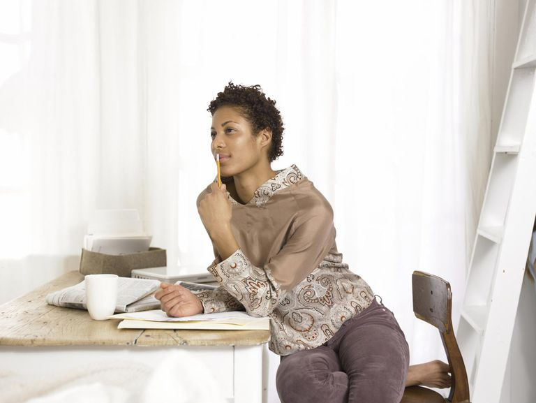 Young woman sitting at table with pencil and paper