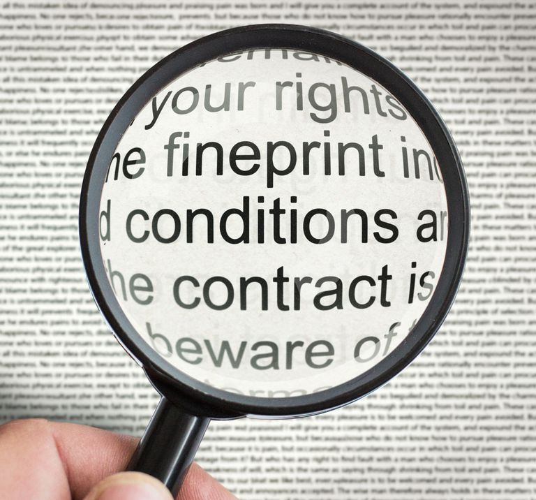 A photo of a magnifying glass over a contract.
