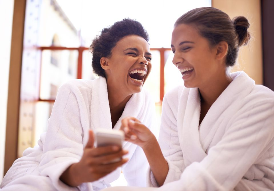 Shot of two friends in bathrobes laughing at a text