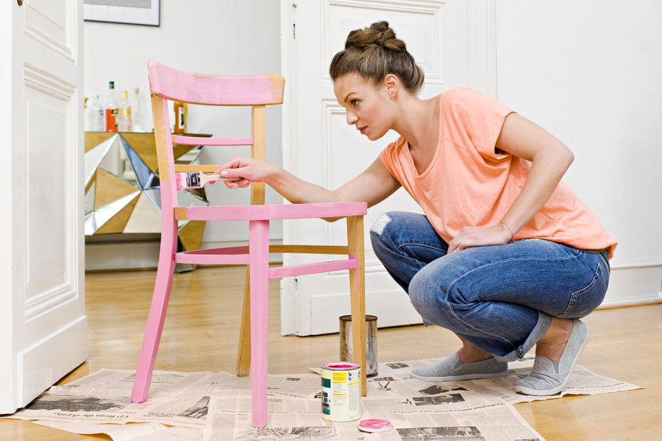 woman painting a chair frame