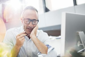 Man on phone in front of computer