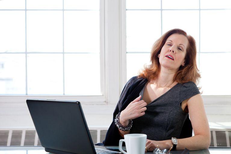 Menopausal woman having a hot flash at the office