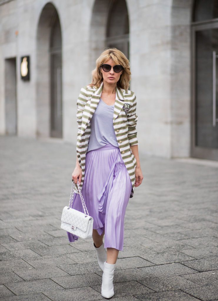 Woman in striped jacket and purple pleated skirt